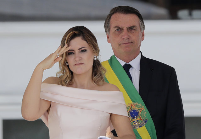 With her husband, Brazil's new President Jair Bolsonaro in the background, Brazil's new first lady Michelle Bolsonaro gives a military salute from the Planalto Presidential palace, in Brasilia, Brazil, Tuesday, January 1, 2019. (Photo by Silvia Izquierdo/AP Photo)
