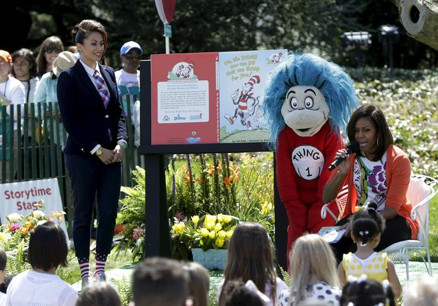 """U.S. first lady Michelle Obama (R) reads """"Oh, the Things You Can Do That Are Good For You"""", a Tish Rabe adaptation of a Dr. Seuss book, to children visiting the White House during the annual Easter Egg Roll in Washington April 6, 2015. At left is Genevieve Goings from the Disney Channel. (Photo by Gary Cameron/Reuters)"""