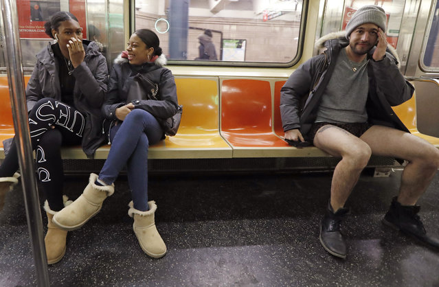 Passengers react to a man seated beside them without pants during the 18th annual No Pants Subway Ride, January 13, 2019, in New York. (Photo by Kathy Willens/AP Photo)