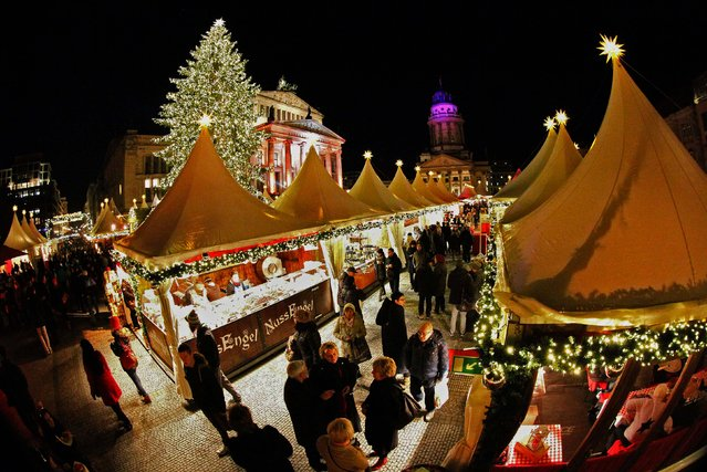 People visit the illuminated Christmas market at Gendarmenmarkt Square in Berlin. (Photo by Fabrizio Bensch/Reuters)