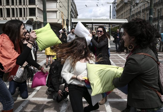 """Youths participate in a pillow fight at a central square of Athens, on Sunday, April 5, 2015.  Pillow fight events are taking place in many cities around the world to mark a so-called """"International Pillow Fight Day"""". (Photo by Yorgos Karahalis/AP Photo)"""