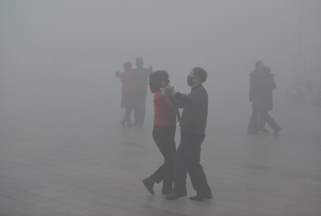 People wearing masks dance at a square among heavy smog during a polluted day in Fuyang, Anhui province, China, January 3, 2017. (Photo by Reuters/China Daily)