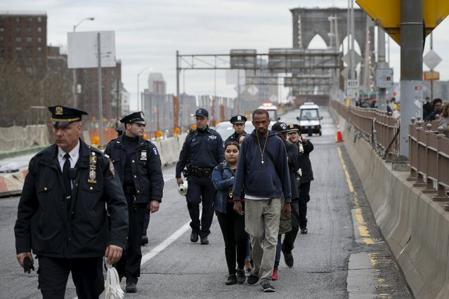 Demonstrators are escorted by the NYPD off the Brooklyn Bridge roadway during a protest against police brutality against minorities in New York, April 14, 201. (Photo by Shannon Stapleton/Reuters)