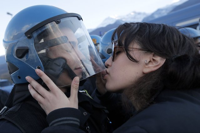 A demonstrator kisses a riot police officer during a protest in Susa, Italy, against the high-speed train (TAV in Italian) line between Lyon and Turin, on November 16, 2013. (Photo by Marco Bertorello/AFP Photo)