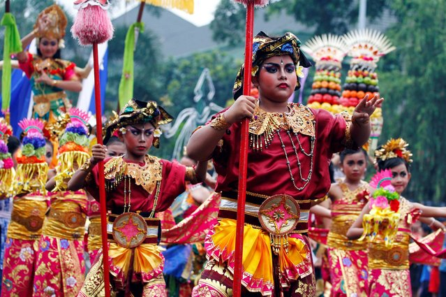 Balinese children wearing traditional costumes dance during a parade for this year's last sundown in Bali island, Indonesia on New Year's Eve, Tuesday, December 31, 2013. (Photo by irdia Lisnawati/AP Photo)