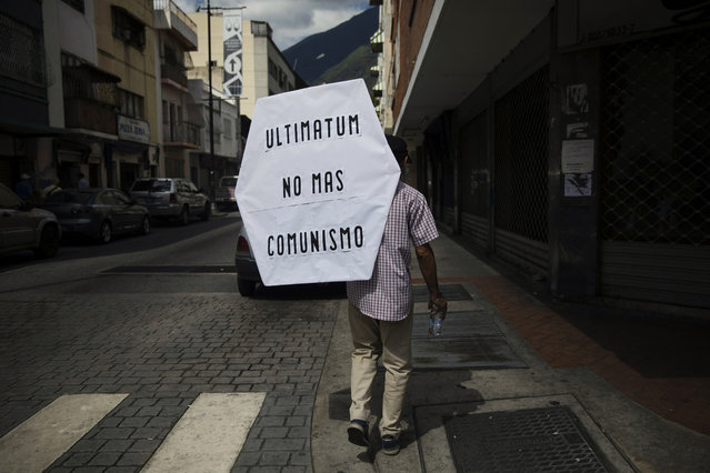 "A supporter of opposition National Assembly leader Juan Guaido, who declared himself interim president, walks with a sign that reads in Spanish: ""Ultimatum, no more communism"" after attending Mass at a church with Guaido in Caracas, Venezuela, Sunday, January 27, 2019. Guaido says he is acting in accordance with two articles of the constitution that give the National Assembly president the right to hold power temporarily and call new elections. (Photo by Rodrigo Abd/AP Photo)"