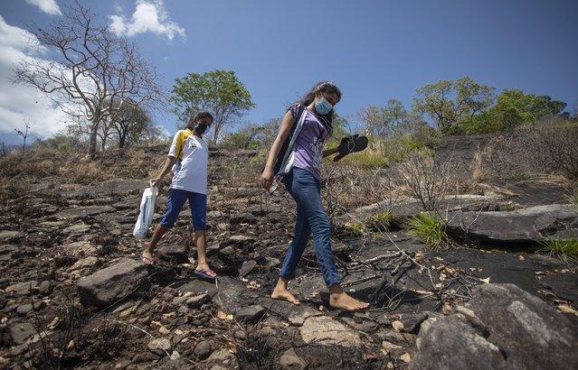 Sri Lankan students walk down a mountain after attending their online lessons in a forest reserve in Bohitiyawa village in Meegahakiwula, Sri Lanka, July 2, 2021. (Photo by Eranga Jayawardena/AP Photo)