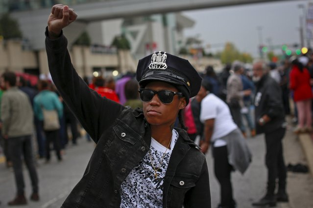 A protester wears a Baltimore police department hat taken out of a police car that was damaged during a rally to protest the death of Freddie Gray who died following an arrest in Baltimore, Maryland April 25, 2015. (Photo by Shannon Stapleton/Reuters)