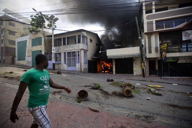 A man walks past a burning car during a protest to demand the resignation of President Jovenel Moise and demanding to know how Petro Caribe funds have been used by the current and past administrations, in Port-au-Prince, Haiti, Thursday, February 7, 2019. Much of the financial support to help Haiti rebuild after the 2010 earthquake comes from Venezuela's Petro Caribe fund, a 2005 pact that gives suppliers below-market financing for oil and is under the control of the central government. (Photo by Dieu Nalio Chery/AP Photo)