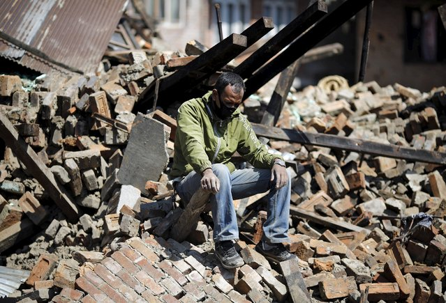 A man sits on the rubble of his damaged house following Saturday's earthquake in Bhaktapur, Nepal April 27, 2015. (Photo by Adnan Abidi/Reuters)