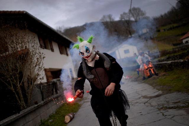 A masked reveller holds a flare during carnival celebrations in Ituren, northern Spain January 30, 2017. (Photo by Vincent West/Reuters)