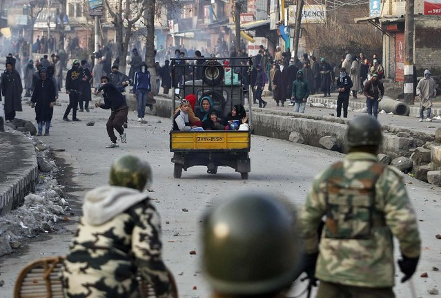 A three-wheeler carrying a family moves past a Kashmiri protester throwing a stone towards the Indian security personnel during a protest in Srinagar January 31, 2014. Shops and other business establishments remained closed in Srinagar on Friday following a shutdown called by the separatists to protest against Indian Army's decision to close an alleged fake encounter case against five soldiers in connection with the killings of five civilians in March 2000 at Pathribal, in south of Srinagar, local media reported. (Photo by Danish Ismail/Reuters)