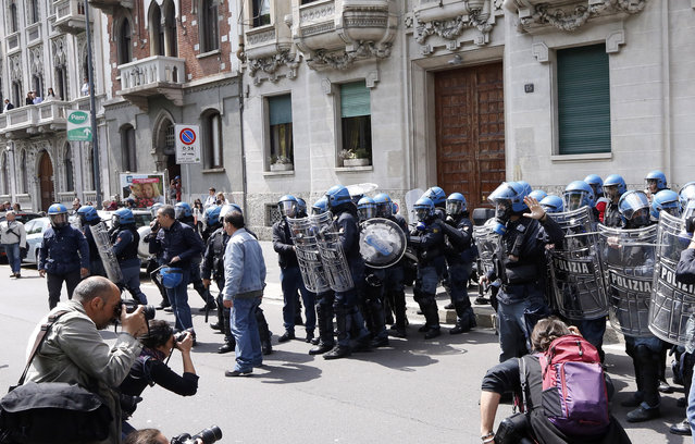 Police in riot gear advance during a protest against Expo 2015 in Milan, Italy, Thursday, April 30, 2015. (Photo by Riccardo De Luca/AP Photo)