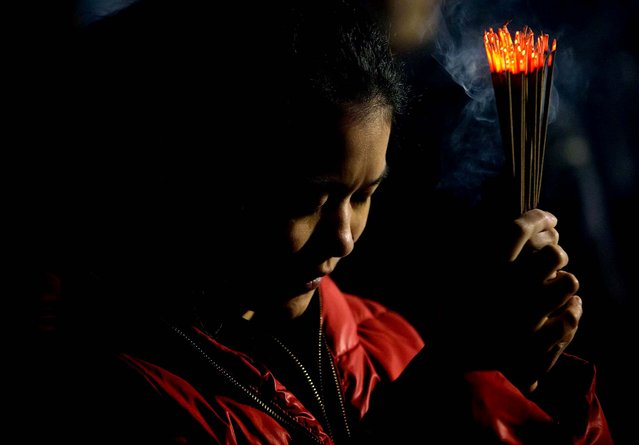 A woman burns incense sticks and prays to mark the Lunar New Year at the International Buddhist Temple in Richmond, British Columbia. (Photo by Darryl Dyck/The Canadian Press)