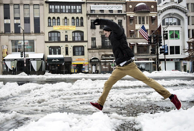 A man jumps over a puddle on Connecticut Avenue in Washington, DC February 13, 2014. The DC area received its first significant winter storm beginning Wednesday night February 12th, with continued mixed winter weather expected throughout Thursday. (Photo by Brendan Smialowski/AFP Photo)