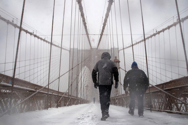 People walk across the Brooklyn Bridge in the snow, February 9, 2017 in New York City. Following a day of 60 degree temperatures, New York City is expected to receive significant snowfall throughout the day on Thursday. (Photo by Drew Angerer/Getty Images)
