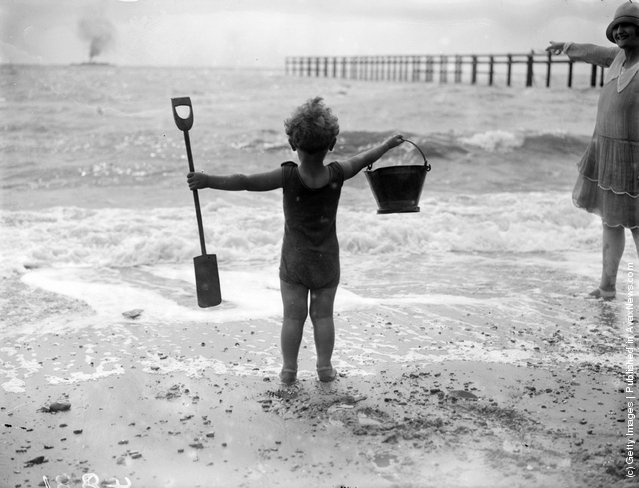 A little boy waves his bucket and spade at the waves as he watches the sea on the beach, 1927