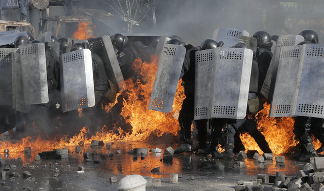 Riot police clash with anti-government protesters outside Ukraine's parliament in Kiev, Ukraine, Tuesday, February 18, 2014. Thousands of angry anti-government protesters clashed with police in a new eruption of violence following new maneuvering by Russia and the European Union to gain influence over this former Soviet republic. (Photo by Efrem Lukatsky/AP Photo)