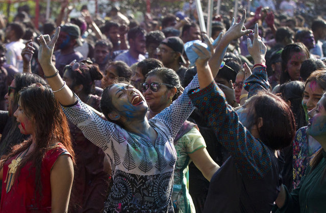 In this Wednesday, March 20, 2019, file photo, revelers dance as they celebrate Holi, also known as the Festival of Colors, organized by the Hindu community at a park in Yangon, Myanmar. (Photo by Thein Zaw/AP Photo)