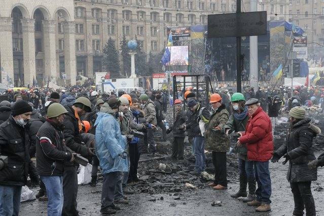 People pass stones to each other to use in attacks against police, during clashes with riot police in Kiev's Independence Square, the epicenter of the country's current unrest, Thursday, February 20, 2014. (Photo by Efrem Lukatsky/AP Photo)