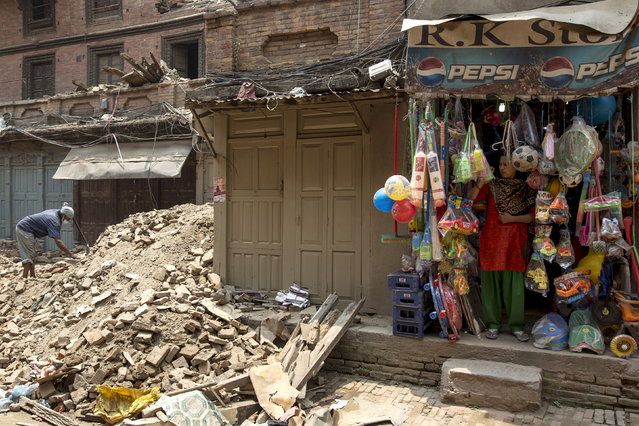 A local resident clears the rubble from the ruins of his home as a vendor stands in front of her shop after the April 25 earthquake, in Bhaktapur, Nepal, May 8, 2015. (Photo by Athit Perawongmetha/Reuters)