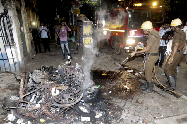 Firemen douse the fire after two wheelers were set on fire during clashes between Bharatiya Janata Party (BJP) workers and students outside the Calcutta University in Kolkata, India, Tuesday, May 14, 2019. Rival political supporters clashed with rocks and sticks during an election rally by the Hindu nationalist party BJP leaving several people injured and a university college vandalized. (Photo by AP Photo)