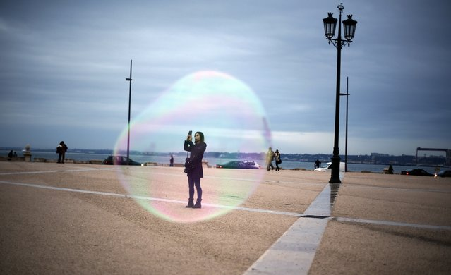A tourist is seen through a soap bubble as she takes a picture at Comercio square in downtown Lisbon November 18, 2014. (Photo by Rafael Marchante/Reuters)