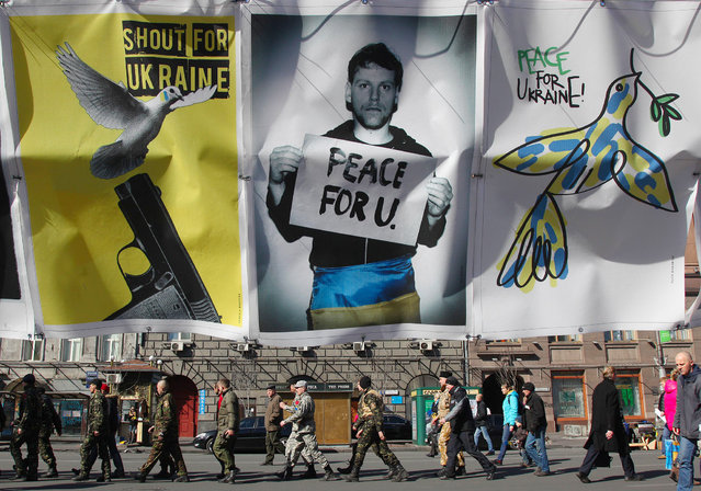 Maidan self-defence activists walk as anti-war placards are hung in  Kiev on March 13, 2014. Ukraine moved Thursday to mobilise a volunteer force to ward off Russia's expansionist threat. (Photo by Anatolii Stepanov/AFP Photo)