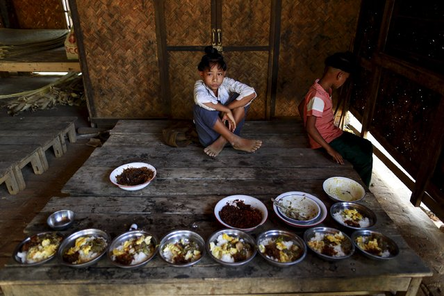 Boys who sort the ancient hairstyle known as Sanyitwine wait for their lunch in a monastery at Sat Sat Yo village in Nyaung Oo township, near Myanmar's ancient city Bagan April 17, 2015. (Photo by Soe Zeya Tun/Reuters)