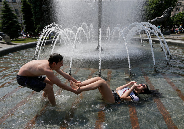 """Secondary school graduates play in a fountain as they celebrate the last day of school, traditionally called the """"last bell"""" in central Kiev, Ukraine on May 31, 2019. (Photo by Valentyn Ogirenko/Reuters)"""