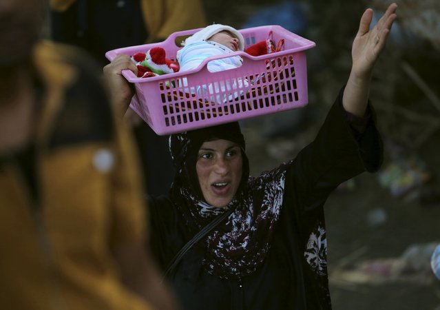 An Iraqi Sunni displaced woman, who fled the violence in the city of Ramadi carries her child on the outskirts of Baghdad, Iraq May 19, 2015. (Photo by Reuters/Stringer)