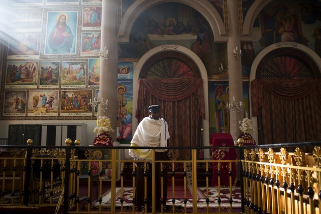 A Christian Orthodox priest stands during morning mass at the Medhane Alem Cathedral in Addis Ababa, Ethiopia, May 18, 2015. (Photo by Siegfried Modola/Reuters)