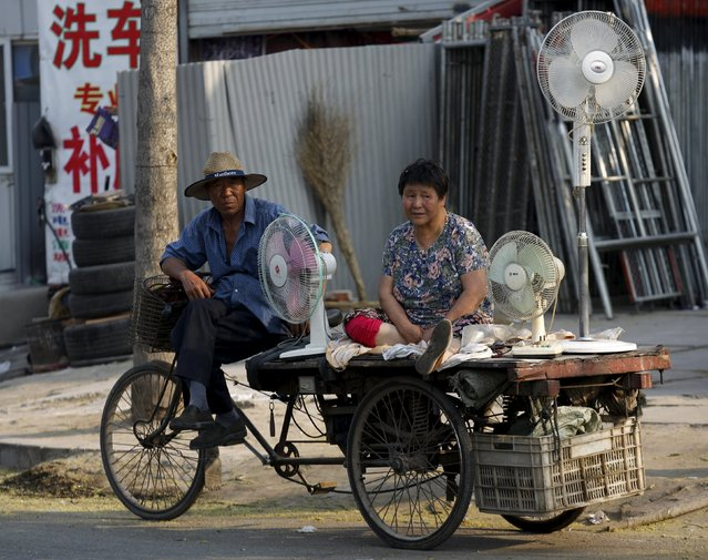 Vendors selling secondhand electric fans wait for customers at a market in  a village for migrant workers in Beijing, China, May 25, 2015. (Photo by Kim Kyung-Hoon/Reuters)