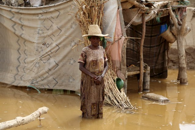 A woman stands near her flooded hut following heavy rain in a village in Yemen's Red Sea province of Houdieda April 15, 2016. (Photo by Abduljabbar Zeyad/Reuters)