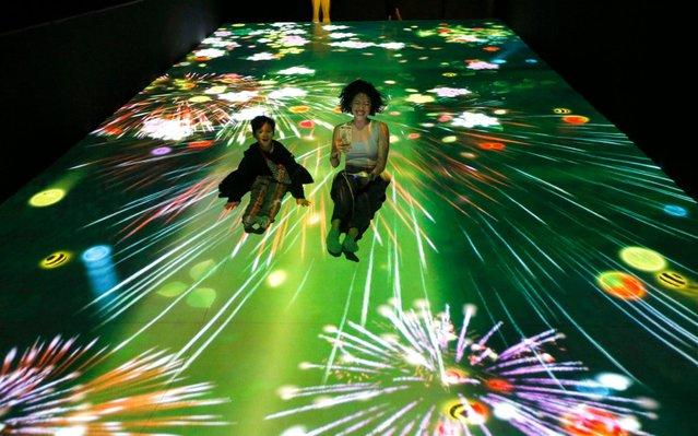 Visitors slide down a platform with a projection of a digital art exhibition titled teamLab Future Park and Animals of Flowers, Symbiotic Lives, at a shopping mall in Jakarta, Indonesia, Wednesday, June 19, 2019. The exhibition that showcases the creation of teamLab, a Japanese digital art company, will be held from June to December 2019. (Photo by Tatan Syuflana/AP Photo)