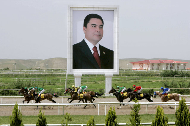 Horses race past a giant portrait of Turkmen President Kurbanguly Berdymukhamedov at the presidential race track in Ashgabat May 11, 2007. (Photo by Reuters/ITAR-TASS/Presidential Press Service)