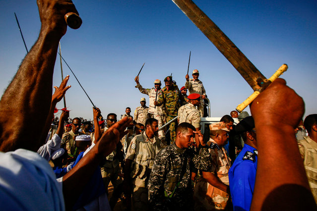Mohamed Hamdan Dagalo (C-R), also known as Himediti, deputy head of Sudan's ruling Transitional Military Council (TMC) and commander of the Rapid Support Forces (RSF) paramilitaries, waves a baton as he rides in the back of a vehicle surrounded by RSF members and crowds of supporters in the village of Qarri, about 90 kilometres north of Khartoum, on June 15, 2019. (Photo by Ashraf Shazly/AFP Photo)