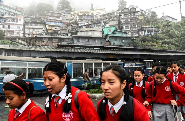 School children walk past a parked Darjeeling Himalayan Railway train, which runs on a 2 foot gauge railway and is a UNESCO World Heritage Site, at a station in Darjeeling, India, June 26, 2019. (Photo by Ranita Roy/Reuters)