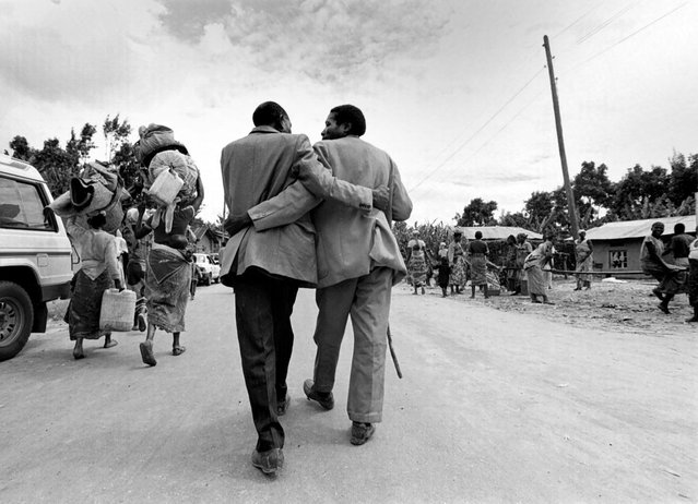 A Rwandan refugee is greeted by a man in the village of Kabiza as thousands return home; 1996. (Photo by Carol Guzy/The Washington Post)