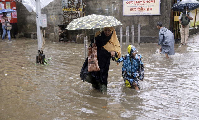 A woman holds the hand of a child and wades through a waterlogged street following rainfall in Mumbai, India, Friday, June 28, 2019. India receives its monsoon rains from June to October. (Photo by Rajanish Kakade/AP Photo)