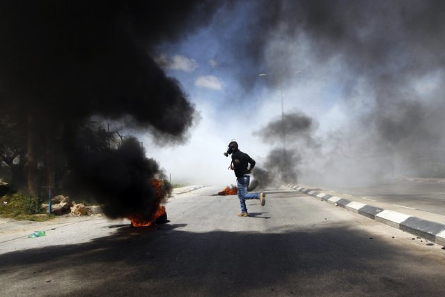 A Palestinian protester runs during clashes with Israeli troops at a protest calling for the release of Palestinian prisoners held in Israeli jails, outside Israel's Ofer military prison near the West Bank city of Ramallah April 4, 2014. Israel has called off a planned release of Palestinian prisoners meant to advance the U.S.-sponsored peace process and called for a review of how the troubled negotiations can make progress, an official briefed on the talks said on Thursday. (Photo by Mohamad Torokman/Reuters)