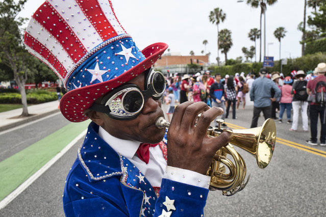 A trumpeter who went only by the name Lenny plays a tune during the Santa Monica Fourth of July parade on July 4, 2019. (Photo by Richard Vogel/AP Photo)