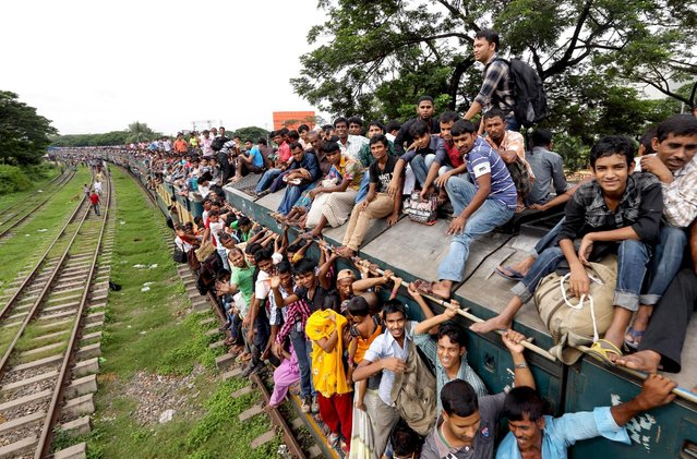 Due to the lack of available space inside, most passengers resort to sitting on top of the train. (Photo by Yousuf Tushar/Solent News & Photo Agency)
