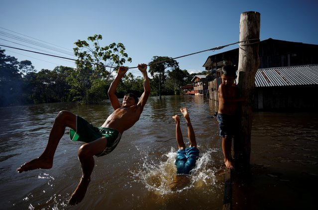 Children play in a street flooded by the rising Rio Solimoes, one of the two main branches of the Amazon River, in Anama, Amazonas state, Brazil on June 24, 2019. (Photo by Bruno Kelly/Reuters)