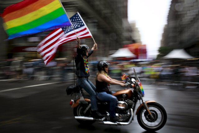A couple carry an American flag and a rainbow flag during the annual Gay Pride parade in New York June 28, 2015. (Photo by Eduardo Munoz/Reuters)