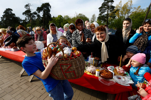 "A boy carries a basket with Easter food, which was donated by believers after an Orthodox priest sprinkled holy water on them and their ""paskha"" cakes, eggs and other food, on the eve of Orthodox Easter outside the church in the town of Bobruisk, Belarus, April 30, 2016. (Photo by Vasily Fedosenko/Reuters)"