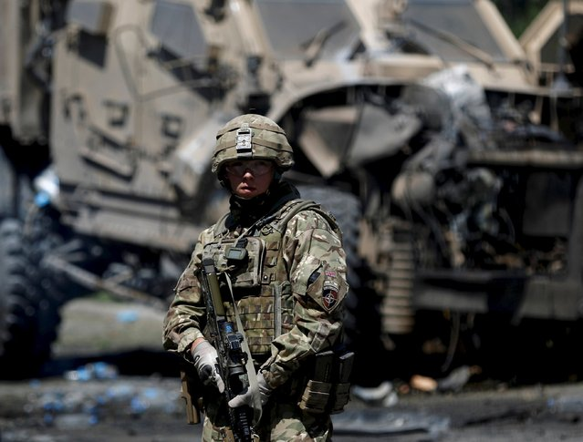 A NATO soldier stands at the site of a suicide bomb attack in Kabul, Afghanistan June 30, 2015. (Photo by Ahmad Masood/Reuters)