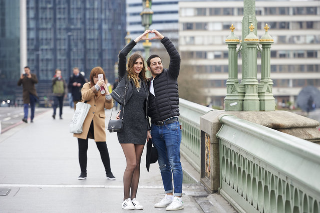 People pose for photographs on Westminster Bridge in central London on March 23, 2017 after the bridge reopened to traffic following its closure during the March 22 terror attack. Britain's parliament reopened on Thursday with a minute's silence in a gesture of defiance a day after an attacker sowed terror in the heart of Westminster, killing three people before being shot dead. Sombre-looking lawmakers in a packed House of Commons chamber bowed their heads and police officers also marked the silence standing outside the headquarters of London's Metropolitan Police nearby. (Photo by Niklas Halle'n/AFP Photo)