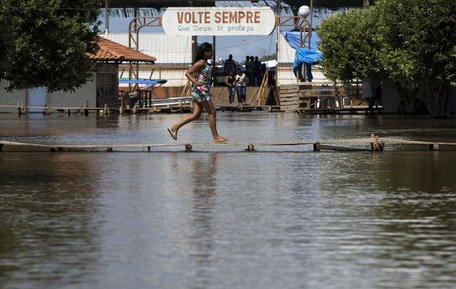 A woman runs on a makeshift walkway above a flooded street from the rising Rio Solimoes, one of the two main branches of the Amazon River, in Careiro da Varzea of Amazonas State, Brazil, June 30, 2015. (Photo by Bruno Kelly/Reuters)