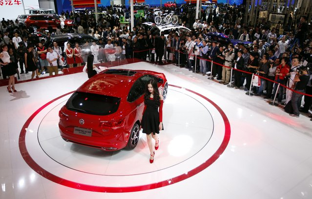 """Visitors gather to look at a GAC Fiat car on display at the """"Auto China 2014"""" Beijing International Automotive Exhibition in Beijing on April 21, 2014. (Photo by AFP Photo)"""